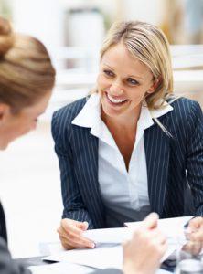 Cheerful young business woman at a meeting with coworkers